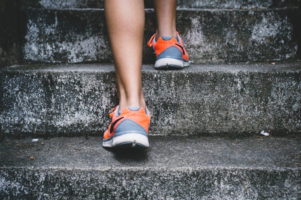 階段を上がる女性の足元(後ろ姿)
