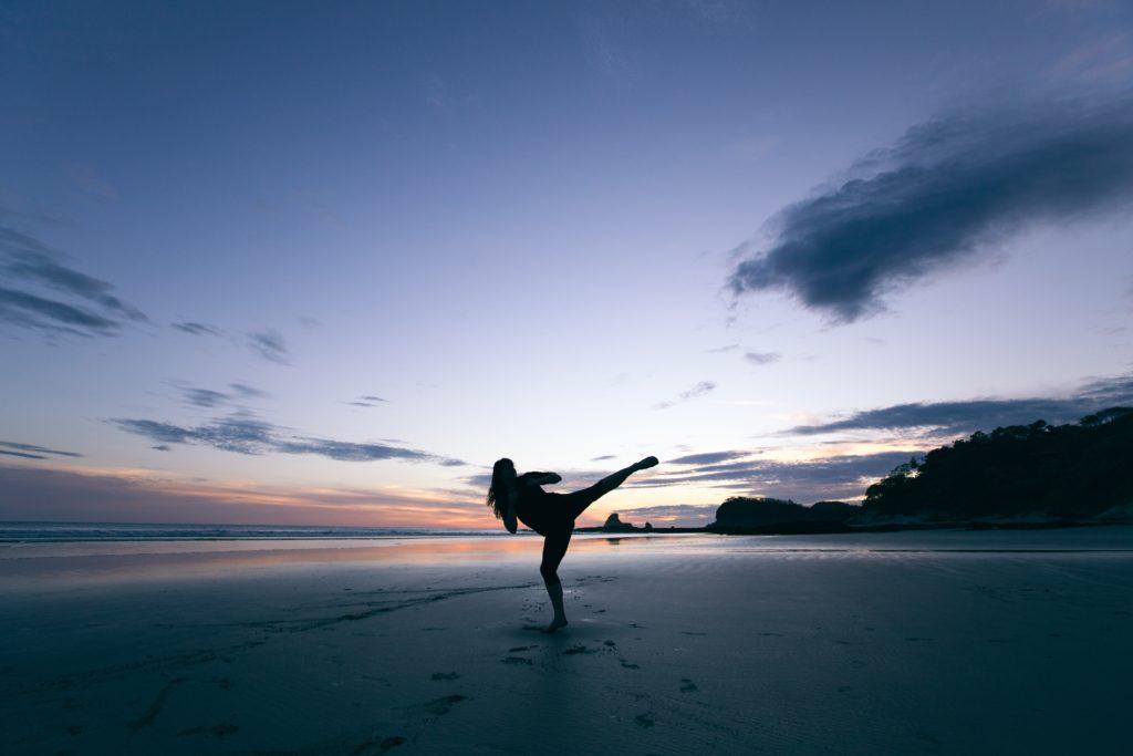 夕暮れのビーチでキックを繰り出す女性
